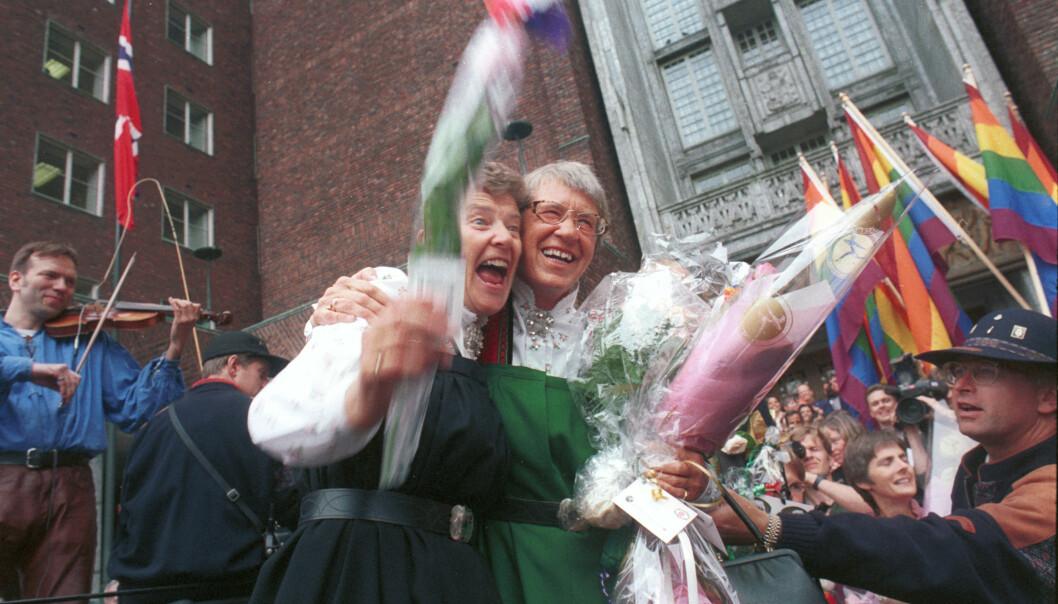 Fem par inngikk partnerskap samtidig i Oslo Rådhus 6. august 1993. På bildet ser vi Kim Friele (tv) og Wenche Lowzow omringet av jublende mennesker med regnbueflagg etter seremonien inne i Rådhuset. I bakgrunnen spiller Øyvind Rauset fele. Foto: Kim Friele/Skeivt arkiv.