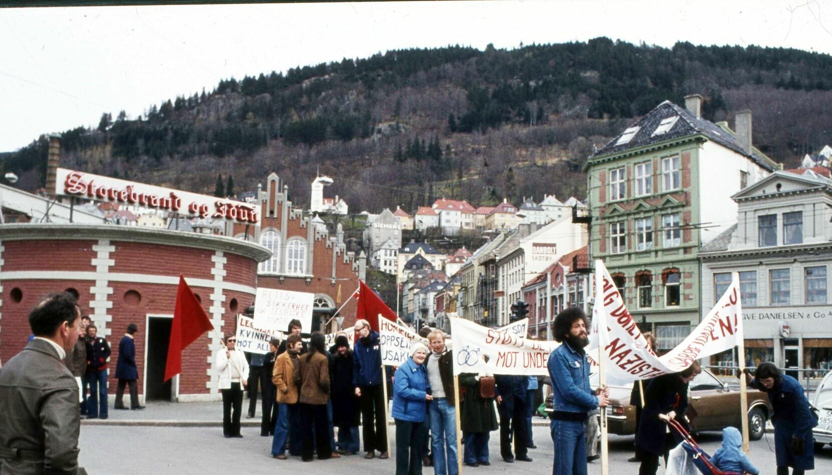 Leif Pareli i grå genser står på Fisketorget i Bergen 1. mai 1976. Han skal bære hovedparolen «Støtt de homofiles kamp mot undertrykking», og for første gang og stå fram som homofil.